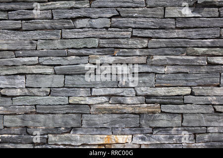 Grey stone granite wall made of stacked pieces stones. Full frame image as background. - Stock Image