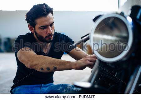 Young male motorcyclist repairing vintage motorcycle outdoors - Stock Image