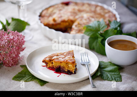 Blackcurrant cake with almond topping and a cup of coffee - Stock Image