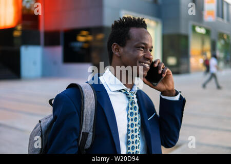 African American businessman holding mobile phone wearing blue suit - Stock Image