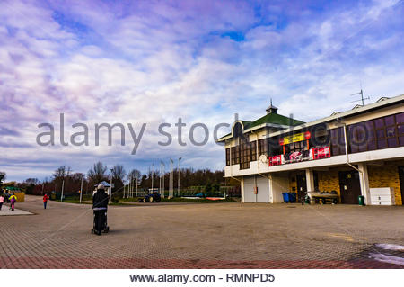 Poznan, Poland - February 10, 2019: Woman with baby buggy walking on a open space close by the Taj India Indian restaurant building in the Malta park  - Stock Image