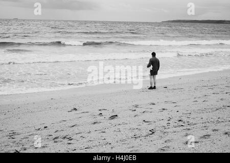Man in a hat stands next to the sea with a towel under his arm as waves come in at Falmouths Gyllyngvase Beach 15 - Stock Image