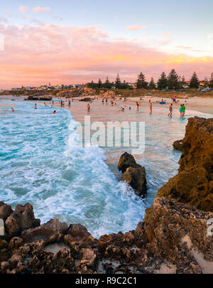 People in the sea at Trigg Beach on a warm summer evening. - Stock Image