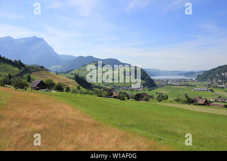 Green meadow and distant view of Lake Lucerne. - Stock Image