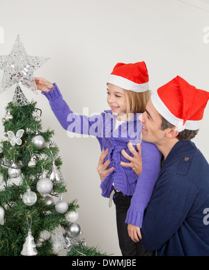 Father And Daughter Looking At Christmas Tree - Stock Image