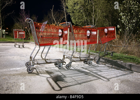 Stray shopping carts lines up in parking lot at night - Stock Image