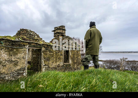 """Ardara, County Donegal, Ireland. 13th March 2019. A farmer looks over his land by the ruins of the old farmhouse. Michael Creed, Ireland's agriculture minister has said today that the UK's decision to impose high tariffs on beef and cheddar in a no-deal scenario are """"potentially a disaster"""" for Irish farmers. Credit: Richard Wayman/Alamy Live News - Stock Image"""