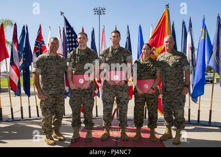 U.S. Marine Corps Brig. Gen. Kevin J. Killea, far right, commanding general, Marine Corps Installations-West (MCI-W), Marine Corps Base (MCB) Camp Pendleton, and Sgt. Maj. Julio Meza, far left, command sergeant major, MCI-W, MCB Camp Pendleton, take a photo with the awarded Marines after the Regional and Installation Marine and noncommissioned officer (NCO) of the Quarter Ceremony at MCB Camp Pendleton, California, Aug. 31, 2018. The Marine and NCO of the Quarter competition was held to recognize Marines that performed exemplary on and off-duty. (U.S. Marine Corps photo by Lance Cpl. Drake Nic - Stock Image