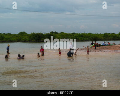 Cambodian families bathing in Tonle Sap lake off a sand bar Siem Reap Cambodia Asia - Stock Image