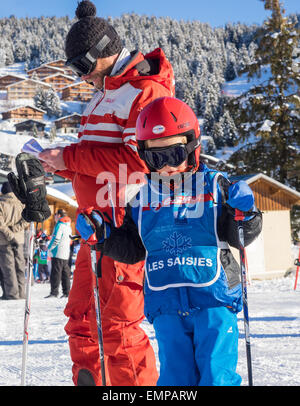 Small child and ski instructor in skiing clothes prior to a skiing lesson with slope and chalets behind - Stock Image