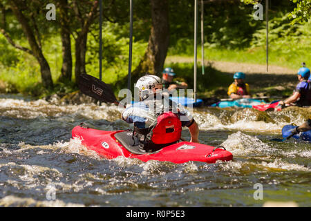 Kayaker paddling the rapids at the National White Water Centre on the River Tryweryn in Snowdonia National Park - Stock Image