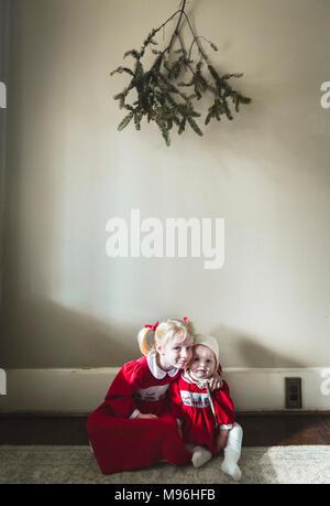 Girl and baby sitting on the floor beneath greenery - Stock Image