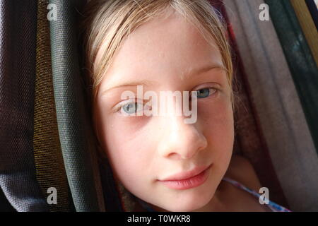 Portrait of a young wet blond girl with blue eyes contently resting in a hammock - Stock Image