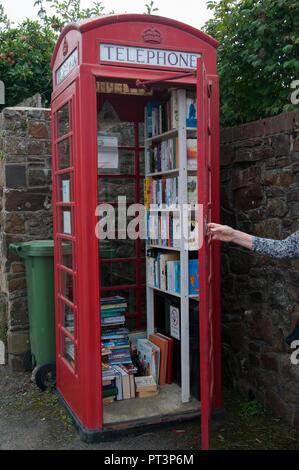 An archetypical British phone box repurposed as a community book exchange, Sheepwash, North Devon, England - Stock Image