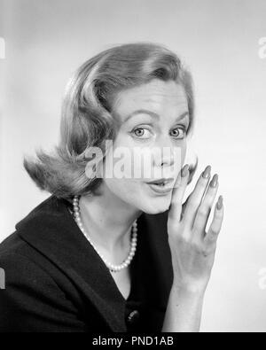 1950s 1960s WOMAN LOOKING AT CAMERA WHISPERING SECRET GOSSIP WITH HAND UP TO MOUTH  - g4585 HAR001 HARS CONFIDENTIAL GOSSIPING EXPRESSIONS B&W EYE CONTACT BUZZ HEAD AND SHOULDERS DISCOVERY BUSYBODY TELLING SCANDAL UP RUMOR STYLISH YENTA ENTRE NOUS CONSPIRATORIAL MID-ADULT MID-ADULT WOMAN SCUTTLEBUTT BLACK AND WHITE CAUCASIAN ETHNICITY HAR001 OLD FASHIONED - Stock Image