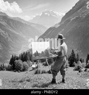 1920s 1930s ARTIST WORKING ON PAINTING STANDING AT EASEL IN BERNESE OBERLAND SWITZERLAND - a1945 LUT001 HARS ALPS BERNESE BACK VIEW CREATIVITY MID-ADULT MID-ADULT MAN BLACK AND WHITE CAUCASIAN ETHNICITY OLD FASHIONED - Stock Image