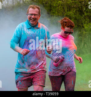 Adult couple running and laughing and being covered in paint on Macmillan cancer charity 5K color fun run. - Stock Image