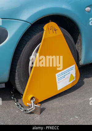 An untaxed car with a wheel clamp on the wheel - Stock Image
