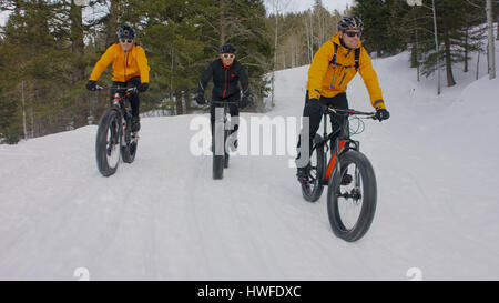 Men riding mountain bikes on remote snowy hillside - Stock Image