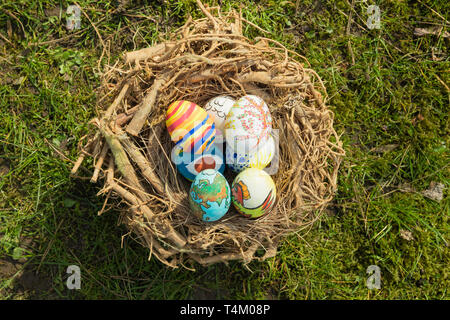Detail of painted Easter eggs with different forms, cartoons and bright colors placed in a bird nest outdoors on a sunny day - Stock Image