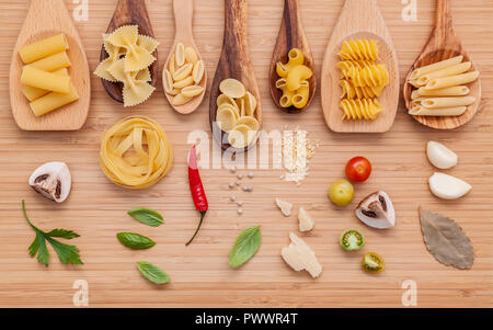 Italian food concept .Various kind of pasta in wooden spoons with ingredients sweet basil ,tomato ,garlic ,parsley ,bay leaves ,pepper ,champignon and - Stock Image
