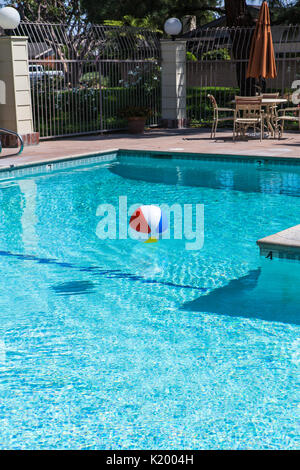 Beachball floating in a beautiful community swimming pool in southern California USA - Stock Image