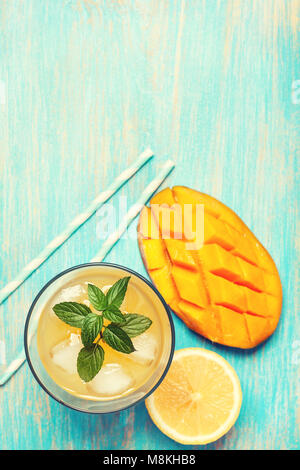 mango ice tea with mint in a glass  on  blue  wooden background . top view. toning - Stock Image