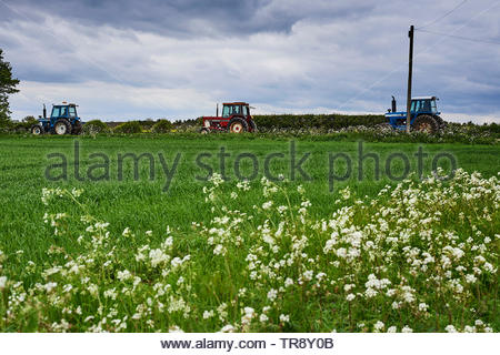 Tractors travelling in Stonesfield in the Cotswolds in Oxfordshire - Stock Image