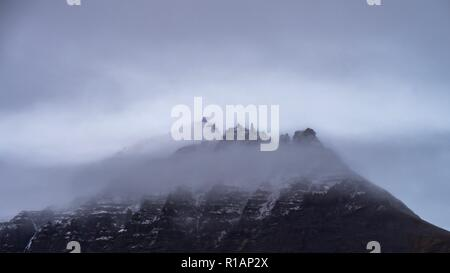 The peaks of mountains appearing through the cloud in southern Iceland - Stock Image