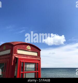 Red telephone box, by the sea. Typical English seaside scene. - Stock Image