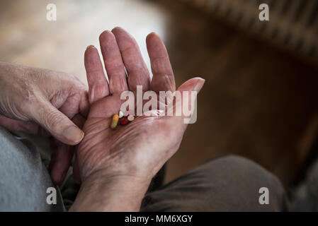 Close up of senior man holding tablets in palm of hand - Stock Image