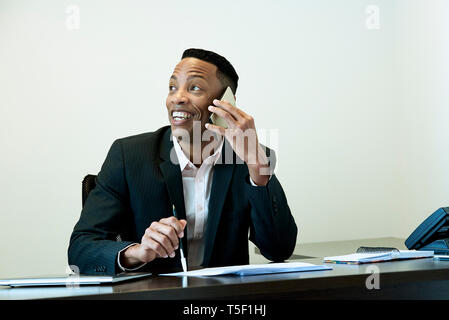 Businessman talking on smart phone in office - Stock Image