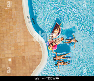 Aerial view of group people having fun together - friends  young tourist women enjoy the pool in summer holiday vacation - coloured inflatable lilos t - Stock Image