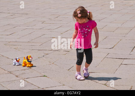 Young girl with pink tee shirt decorated with heart and flowers pulls two toy dogs on string in Campo San Stefano - Stock Image