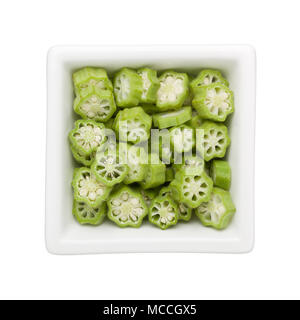 Sliced okra in a square bowl isolated on white background - Stock Image