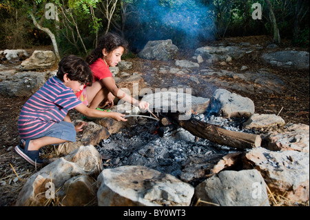 kids in a campfire in a mediterranean forest - Stock Image