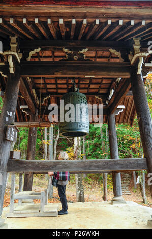 A female foreign tourist exploring the belltower of a Shinto shrine at Hida-no-Sato folk village, Takayama, Japan - Stock Image