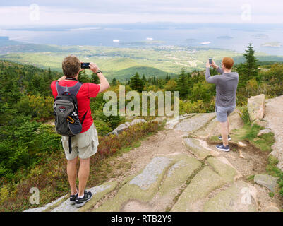 Visitors taking pictures of Frenchman Bay with their cellphones from the top of Cadillac Mountain in Acadia National Park, Maine, USA. - Stock Image