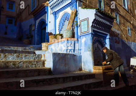Chefchaouen, Morocco : A man washes a handful of mint leaves at a fountain in the blue-washed alleyways of the medina old town. - Stock Image