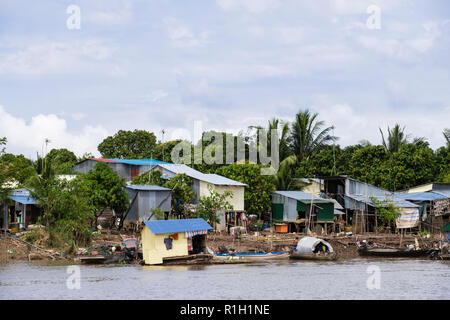Typical tin houses shacks on stilts in fishing village along Mekong River. Cambodia, southeast Asia - Stock Image