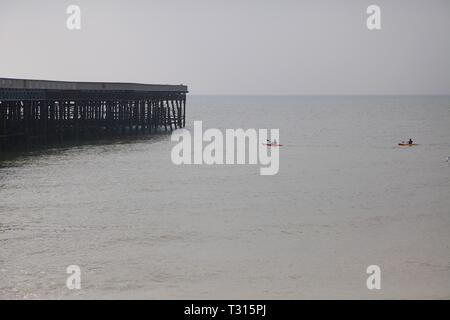 Hastings, East Sussex, UK. 06 Apr, 2019. UK Weather: Mild but overcast in the seaside town of Hastings in East Sussex this morning, highs of 12 degrees centigrade. Kayakers approach the Hastings pier in the calm sea waters. © Paul Lawrenson 2019, Photo Credit: Paul Lawrenson/Alamy Live News - Stock Image