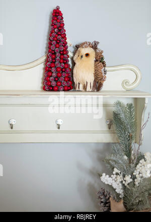 A red tabletop Christmas tree and owl decorations on a wall shelf. - Stock Image