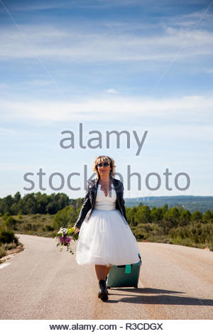 Bride with black leather jacket, sunglasses, a suitcase and a bouquet walks in the middle of a lonely road. - Stock Image