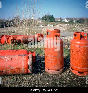 Dumped gas cylinders on urban wasteland near a residential area in Liverpool, UK. - Stock Image