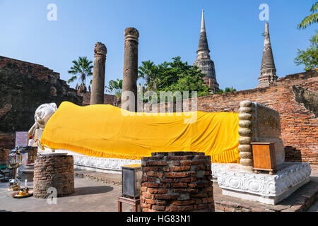 Buddha statues are white covered with yellow robe poses sleep amidst ancient ruins at Wat Yai Chai Mongkon temple - Stock Image