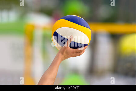 Volleyball is a volleyball player holding up a volleyball getting ready to serve. - Stock Image