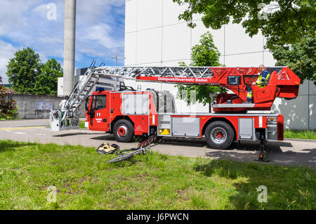 Side view of an Iveco Magirus 160E30 turntable ladder truck of a Swiss fire brigade. Outriggers/jacks extended, - Stock Image