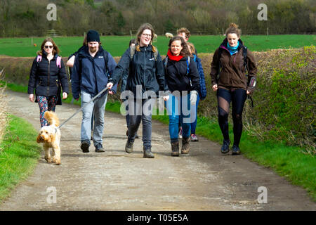 A group of young men and women and a dog walking on a country lane in Great Ayton North Yorkshire - Stock Image