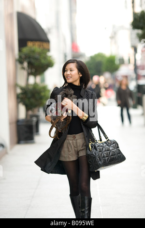 A young woman is walking through a crowded city street holding a canine companion. - Stock Image