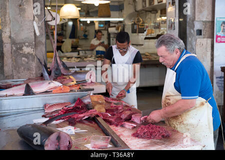 Fishmongers cutting fillets of fish - tuna cutlets - on market stall at street market - Mercado -  in Ortigia, Syracuse, Sicily - Stock Image